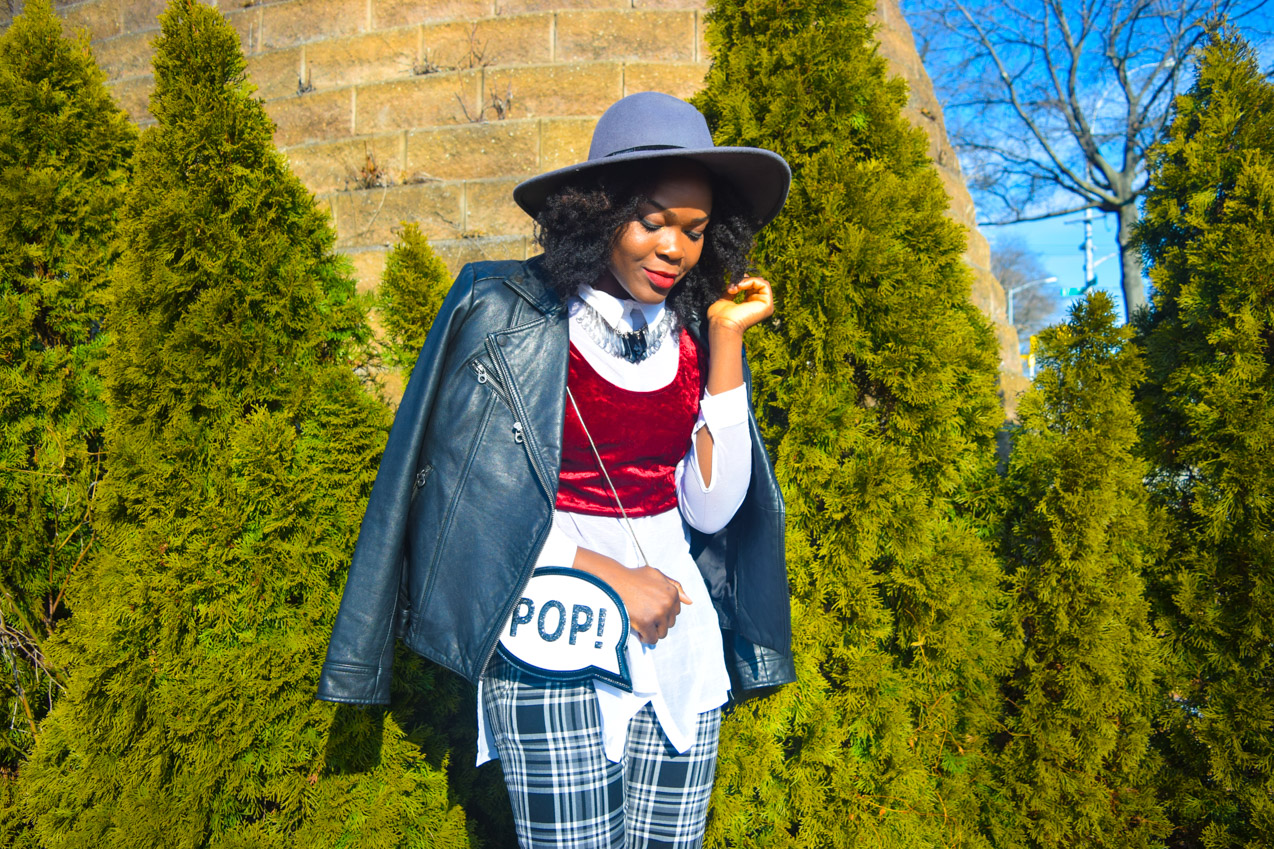 Oyinkan wearing black and white plaid pants with leather biker jacket and brim hat